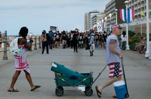 People walk by as Black Lives Matter protesters march on the boardwalk at 11th Street in Virginia Beach (Kristen Zeis/The Virginian-Pilot via AP)