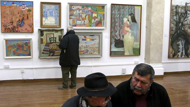 A man looks at paintings during an exhibition at the Ledra Palace Hotel inside the UN-controlled buffer zone in divided capital Nicosia, Cyprus (Petros Karadjias/AP)