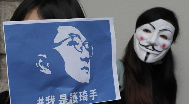 A supporter holds a placard with picture of Hong Kong activist Edward Leung (KIn Cheung/AP)
