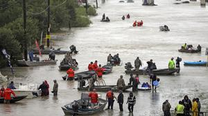 Rescue boats fill Tidwell Road in Houston as they help flood victims evacuate (AP Photo/David J. Phillip)