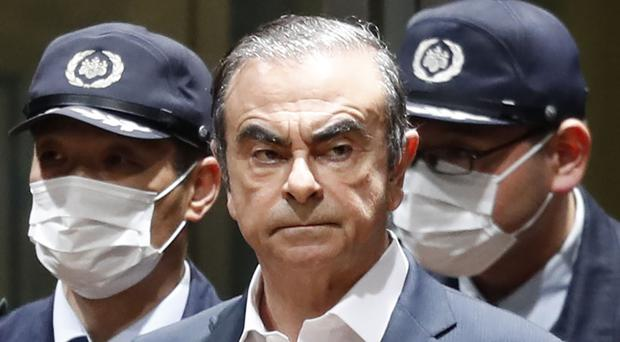 In this photo from April, former Nissan Chairman Carlos Ghosn leaves Tokyo's Detention Centre for bail in Tokyo (Kyodo News/AP/File)