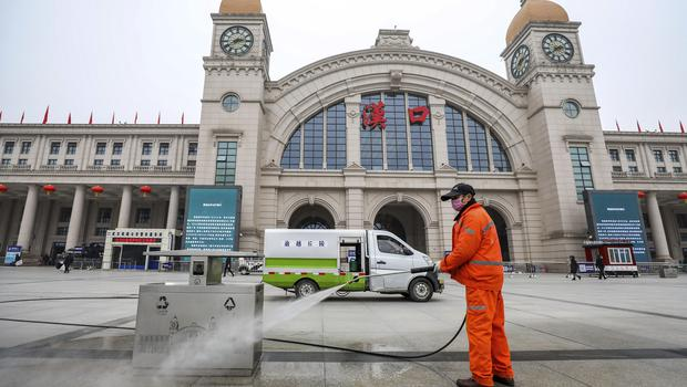 A worker hoses down garbage bins outside the closed Hankou Railway Station in Wuhan on Thursday (Chinatopix/AP)