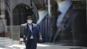 A man wearing a face mask to help curb the spread of the new coronavirus is reflected on a show window of a tailor in Tokyo (Eugene Hoshiko/AP)