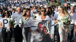 Veronique Monguillot, wife of Philippe Monguillot, holds a photo on a march (AP)