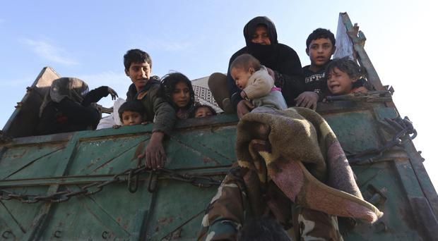 A baby is lifted onto a truck carrying civilians fleeing Maaret al-Numan in Syria, ahead of a government offensive (Ghaith al-Sayed/AP)