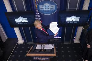 President Donald Trump flips through a stack of papers as he speaks about the coronavirus in the James Brady Press Briefing Room of the White House (AP)