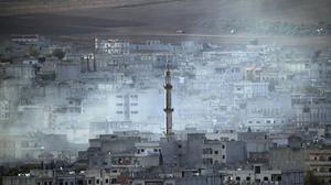 Smoke rises following a strike in Kobani, Syria, as fighting continues between Syrian Kurds and the militants of Islamic State group (AP)