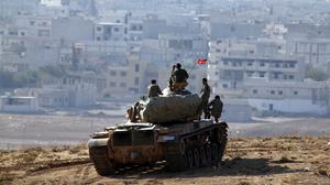 Turkish troops on a hilltop on the outskirts of Suruc, at the Turkey-Syria border, overlooking Kobani. (AP)