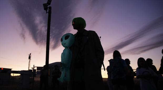 Chase Hansen holds an inflatable alien near an entrance to the Nevada Test and Training Range near Area 51 (AP)