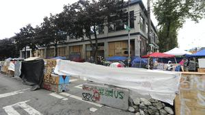 Cement barricades are fortified with chunks of concrete and tarps in front of the Seattle Police Department East Precinct building, Tuesday, June 30, 2020 at the Chop (Capitol Hill Occupied Protest) zone in Seattle (Ted S. Warren/AP)
