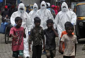 Health workers wearing protective clothing arrive to screen people for Covid-19 symptoms at a slum in Mumbai, India (Rafiq Maqbool/AP)