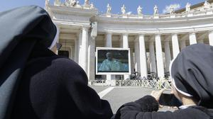 Nuns watch Pope Francis on a giant screen on Sunday as he delivers the Angelus, in St Peter's Square, at the Vatican (Andrew Medichini/AP)