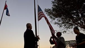 Workers at Havana's Armadores de Santander hotel lower the United States flag at sunset (AP)