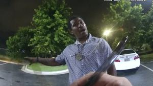 This screen grab taken from body camera video provided by the Atlanta Police Department shows Rayshard Brooks speaking with Officer Garrett Rolfe as Rolfe writes notes during a field sobriety test in the parking lot of a Wendy's restaurant, late Friday, June 12, 2020, in Atlanta. Rolfe has been fired following the fatal shooting of Brooks and a second officer has been placed on administrative duty. (Atlanta Police Department via AP)