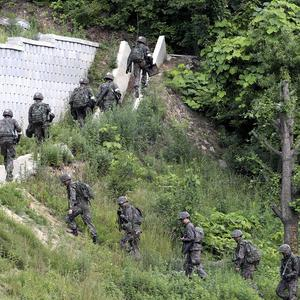 South Korean military authorities have surrounded a soldier who fled his border outpost after killing five comrades, a defence official said (AP)