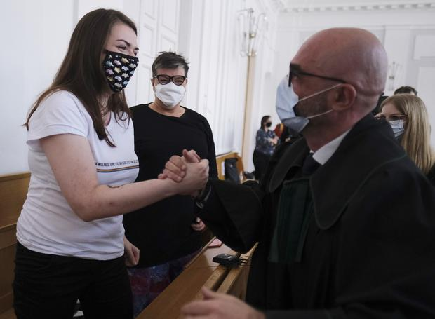 Anna Prus, left, shakes hands with her lawyer (Czarek Sokolowski/AP)