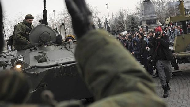 A Russian army officer helps an armoured personnel carrier drive on a street in Sevastopol (AP)