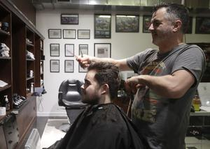 Cathedral Junction Barbers owner Conrad Fitz-Gerald cuts the hair of his son Heathcliff (Mark Baker/AP)
