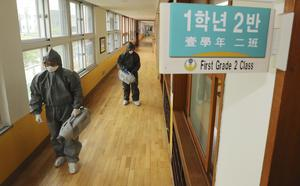 Workers disinfect as a precaution against the new coronavirus ahead of school reopening at an elementary school in Gwangju, South Korea (Park Chul-hong/AP)