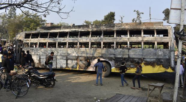 People look at the charred remains of the bus involved in the incident (AP)