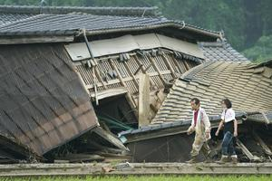 A couple walk in front of houses damaged by a flood in Kuma village (Koji Harada/AP)