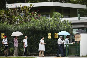 Voters wear face masks and observe social distancing as they line up to vote (AP)