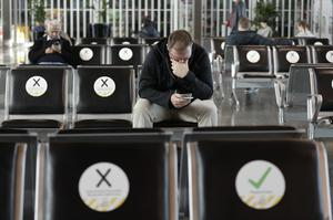 Passengers wait to board their flight at Christchurch Airport in New Zealand where only some seats are marked as free to sit on to encourage social distancing (Mark Baker/AP)