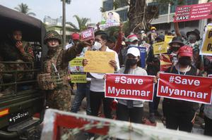 Protesters and soldiers outside the Central Bank of Myanmar building in Yangon (AP)