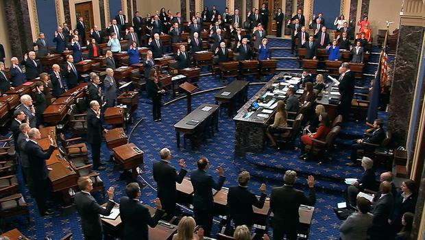 Supreme court chief justice John Roberts swears in members of the senate for the impeachment trial (Senate Television/AP)