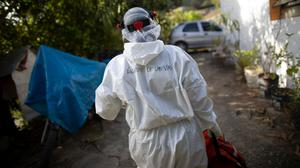 Wearing a biosecurity suit, Dr Debora Mejia, an Angels of the Road volunteer, walks out of a house after visiting two Covid-19 patients in Caracas, Venezuela (Ariana Cubillos/AP)