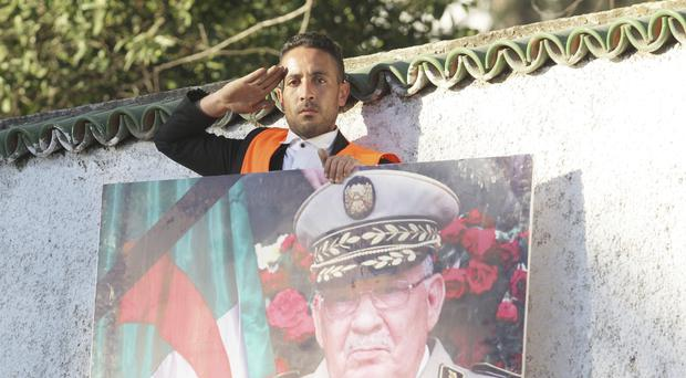 A man gives the military salute during the funeral of late Algerian military chief Gaid Saleh in Algiers (Fateh Guidoum/AP)