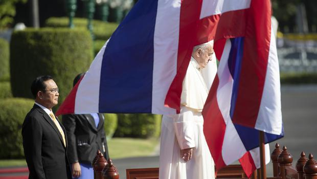Pope Francis, right, and Thailand's Prime Minister Prayuth Chan-ocha listen to the national anthems during a welcoming ceremony at the government house in Bangkok on Thursday (Sakchai Lalit/AP)