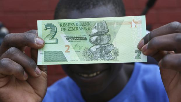 A man holds one of the new two-dollar banknotes issued by the Reserve Bank of Zimbabwe in Harare, Tuesday, Nov, 12, 2019. The Reserve Bank of Zimbabwe began issuing new notes and coins on Tuesday, aimed at easing crippling cash shortages amid run away inflation.(AP Photo/Tsvangirayi Mukwazhi)