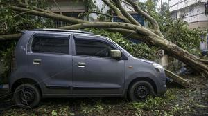 A damaged car after an uprooted tree fell on it after Cyclone Amphan hit the region in Kolkata, India, Thursday, May 21, 2020. A powerful cyclone ripped through densely populated coastal India and Bangladesh, blowing off roofs and whipping up waves that swallowed embankments and bridges and left entire villages without access to fresh water, electricity and communications. (AP Photo/Bikas Das)