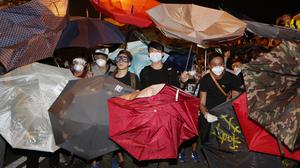 Protesters use umbrellas to block the pepper spray used by police officers at the main roads outside government headquarters in Hong Kong's Admiralty (AP)