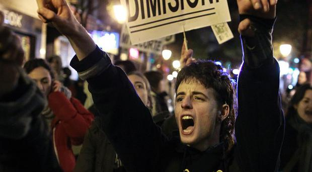 Protesters shout as they carry a banner reading 'Resign' during a demonstration against corruption in Madrid (AP)