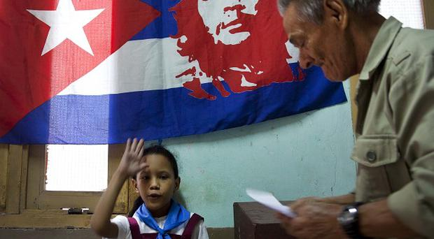Under a Cuban flag with an image of Ernesto 'Che' Guevara, a schoolgirl raises her hand confirming a voter is properly casting his ballot in Havana (AP)