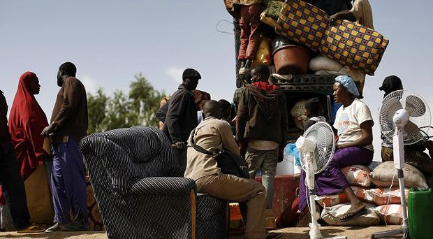 Malians load a pickup truck with goods and furniture as they arrive after crossing the Niger river at Korioume Port, south of Timbuktu (AP)