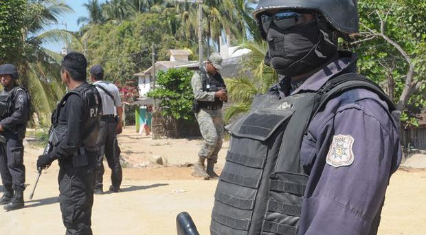 Mexican police at a roadblock in Acapulco amid stepped up security after masked armed men broke into a home and raped six Spanish tourists (AP)