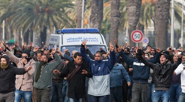 Protesters gather at the ambulance carrying the body of opposition leader Chokri Belaid in Tunis (AP)