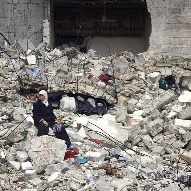 A Syrian woman sits on the ruins of her house following an air strike in Aleppo (AP)