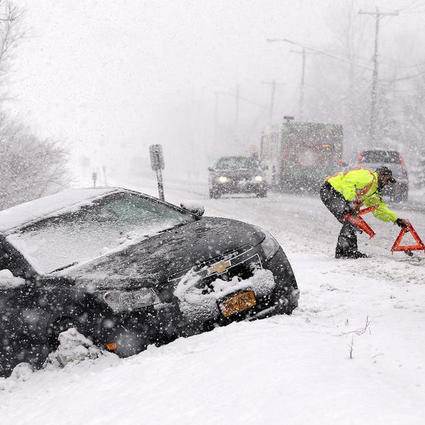 Tow truck operator Shawn Juhre sets up road safety reflectors before towing a car out of a ditch during a winter storm in Buffalo, New York (AP)
