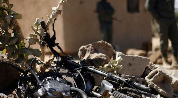 Malian soldiers stand by the remains of a motorcycle used by a suicide bomber at the entrance of Gao, northern Mali (AP/Jerome Delay)