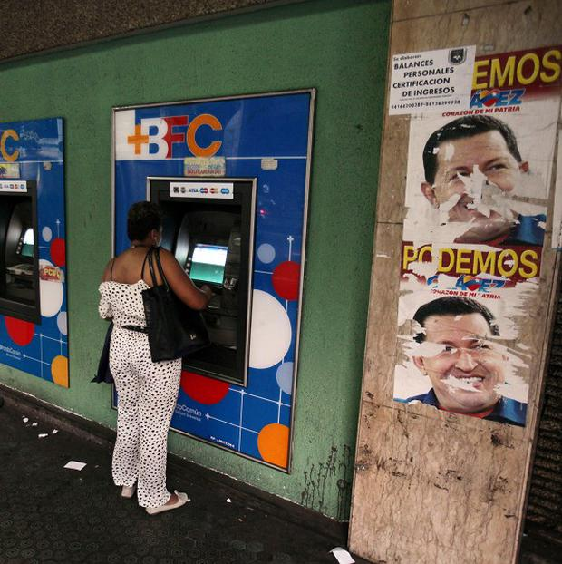 People withdraw money from cash machines next to posters of President Hugo Chavez in Caracas, Venezuela (AP)