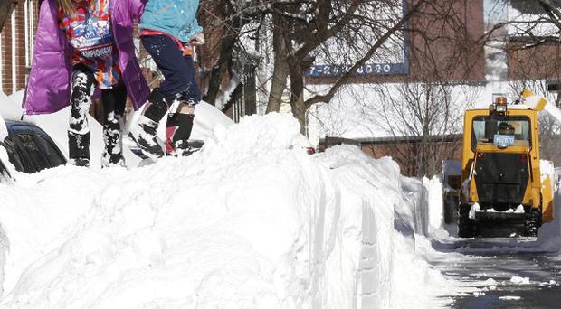Riley Clark, left, and her sister Mckenzie play on top of a pile of snow as the street is cleared (AP Photo/Winslow Townson)