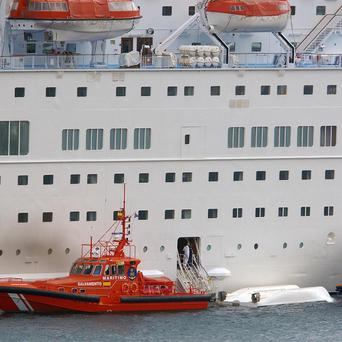 An orange rescue boat docks by a capsized lifeboat from the British-operated cruise ship Thomson Majesty (AP)