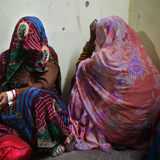 Women grieve the death of their family members after a stampede at a railway station in Allahabad (AP)