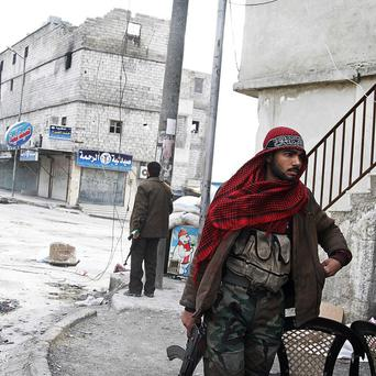 A Free Syrian Army fighters patrols close to the front lines near a main highway in Aleppo (AP)