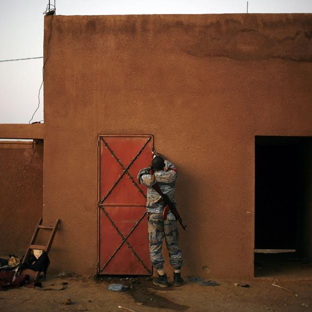 An officer closes a cell where suspected Islamist rebel group the Movement for Oneness and Jihad in West Africa fighters are held in Mali (AP)