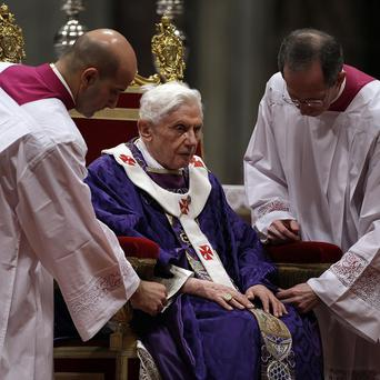 Bishop Guido Marini, right, and an unidentified master of ceremonies adjust Pope Benedict XVI's robe during the Ash Wednesday Mass (AP)